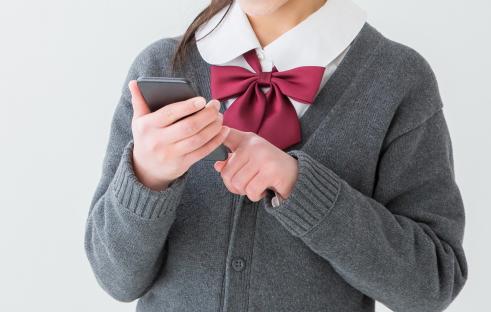 スマホを使用する女子学生の写真