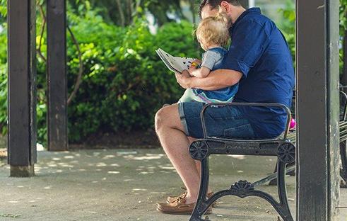 子供にスマホではなく本を読ませる男性の写真